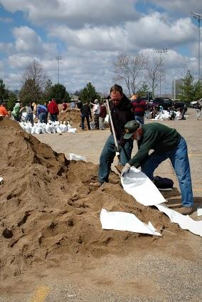 Volunteers load sandbags in an effort to keep flood waters at bay for downtown Peoria businesses.