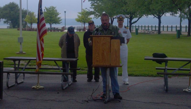 Neill Voges, Navy Commander for Navy Club Ship 43 honors maritime service banches during a Memorial Day ceremony