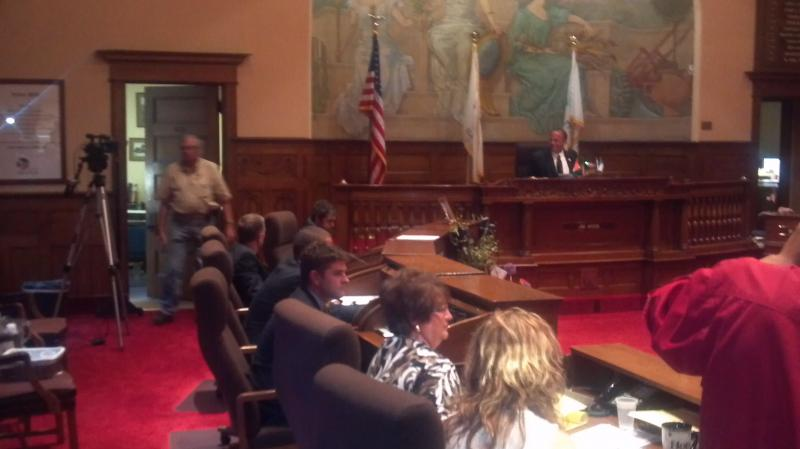 Peoria City Councilman Gary Sandberg's son is seated at his father's desk for the last moments of the council meeting.