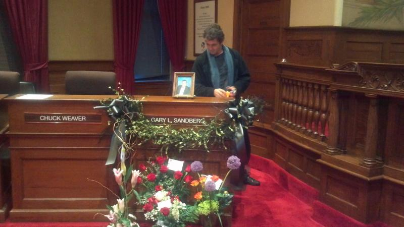 Peoria City Councilman Gary Sandberg's son looks at his father's desk  at the council horseshoe.