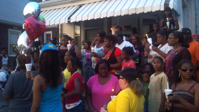 Friends and family share candles for the vigil at the 810 S Western Ave residence of 8-year-old Marquail Johnson.