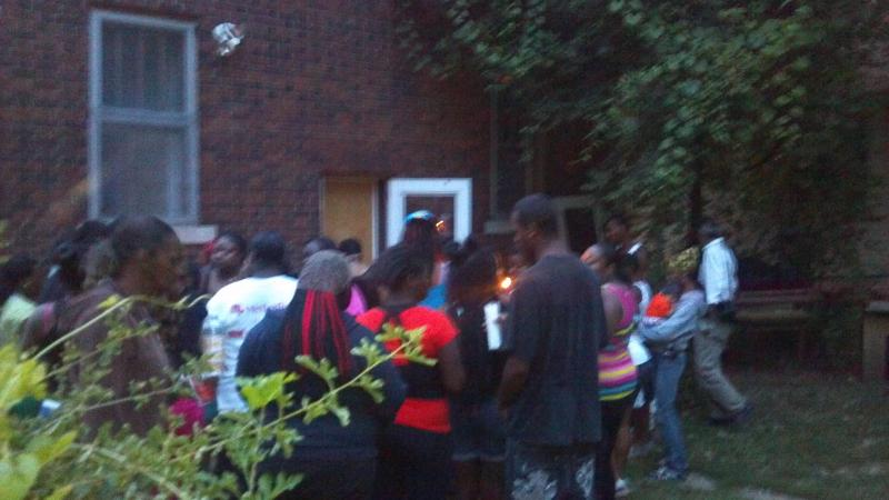 The Marquail Johnson vigil gathers in the back yard of the 740 S Western Ave address where he was found Thursday morning in a latched refrigerator in the back yard.