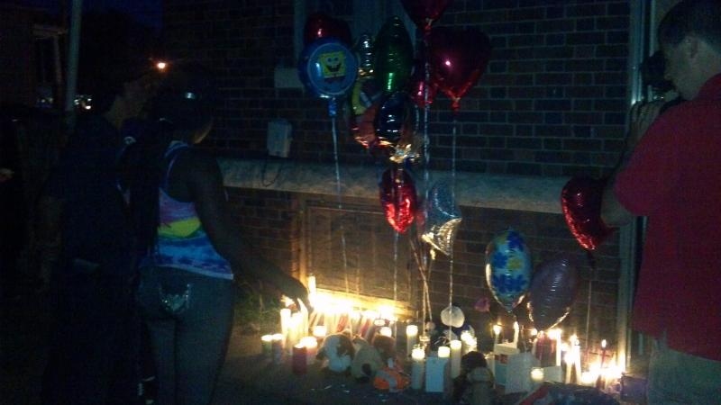 The place 8-year-old Marquail Johnson's life ended 24-hours before is lit with candles and balloons placed in his honor.  The child was found in an old latched refrigerator Thursday morning int eh back yard of the 740 S Western Ave address in Peoria.