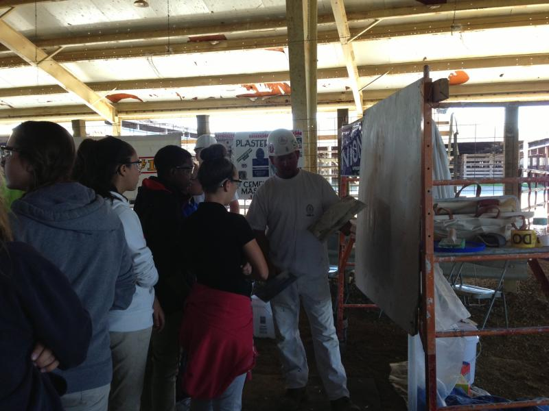 District 150 students learn how to plaster a wall.