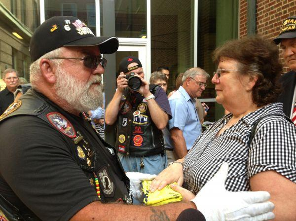 Rick Daley of the Illinois Patriot Guard presents Cindy Morrison with a flag signed by more than 30 members of the patriot guard who came out for the dedication.