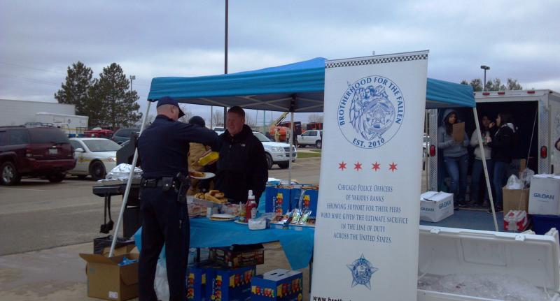 Chicago Police Officers offer emergency workers a bite to eat. They also brought rubber totes with lids for people to use for storeage.  The are set-up in the side parking lot  at Five Points Washington