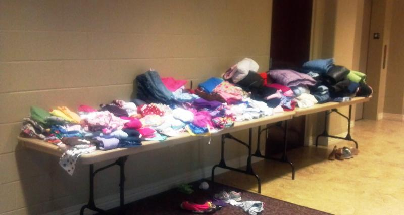 Gently used children's clothes occupy several tables at Five Points Washington.