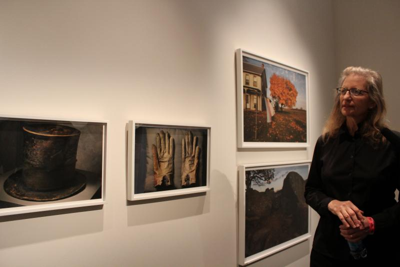 Annie Leibovitz looks at photos from her exhibit at the Abraham Lincoln Presidential Museum in Springfield. At left are Lincoln's hat and gloves he had with him the night of his assassination.