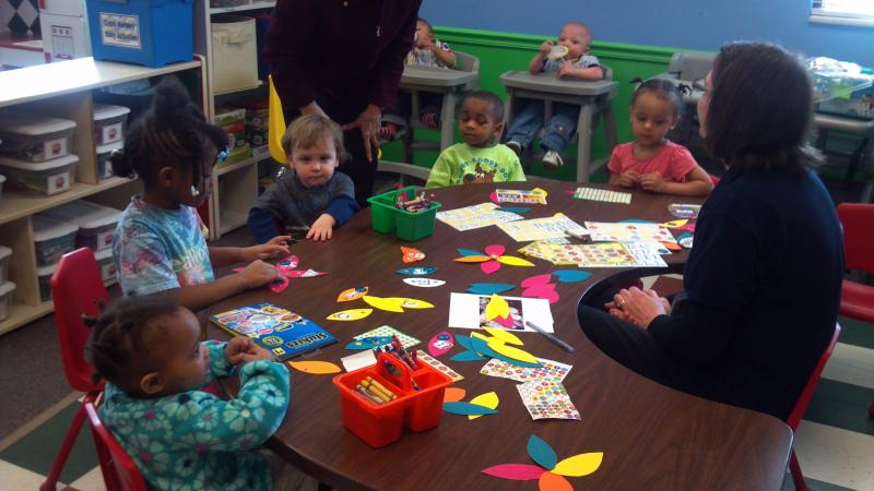 The children, most who are 3, at Crittenton Centers are cutting out petal shapes to past together flowers for Spring.