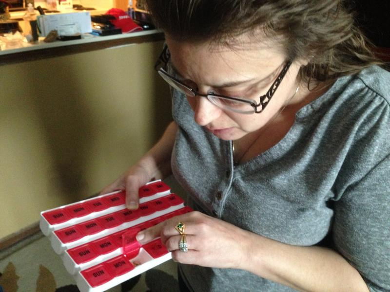 Holly Brandt shows her medication at her home in St. Joseph, Il.