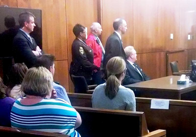 Leuthold stands durning the reading of his guilty verdict. His defense attorney is seated next to him.