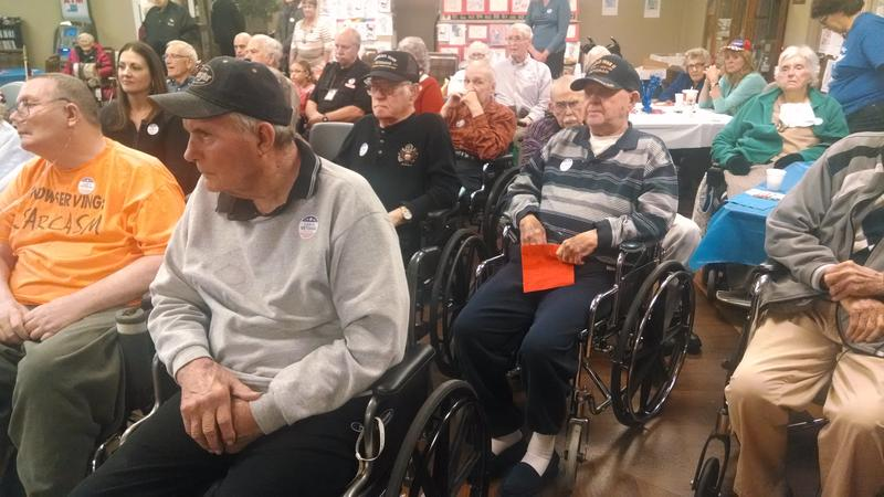 Veterans and other Heddington Oaks residents attend the Veteran's Day ceremony in the community room.