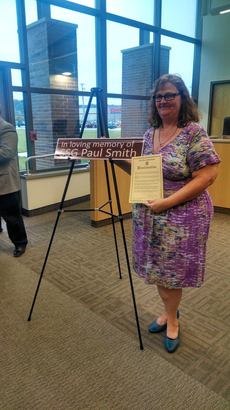 Kim Smith holds a proclamation from the mayor and stands next to the honorary sign the City of East Peoria placed at her street.