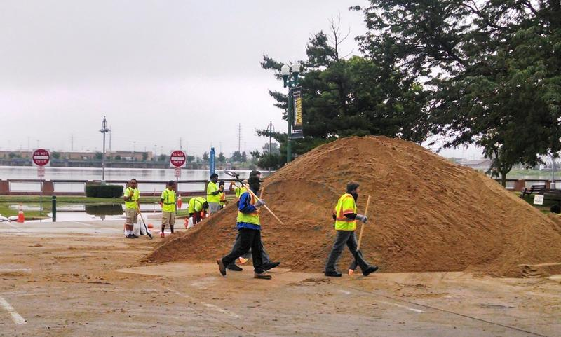 Members of the Mayor Youth Summer Program and Peoria  Public Works working on the flood wall as the Illinois River is creeping beyond its bank in downtown Peoria near Joe's Crab Shack and the River Station.