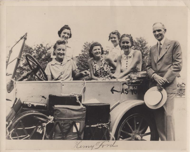 Henry Ford stands proudly next to his creation, the Model T with the Gypsy Coeds in Detroit during their 1938 trip.