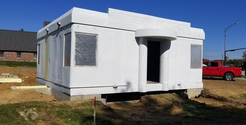 The Steel House sits on its new foundation at the Wheels O' Time Museum. It's primed and ready for paint. Notice the handles at the lower part of the house. The handles allow a crane to pick up the house and move it. There are similar hooks on the roof.