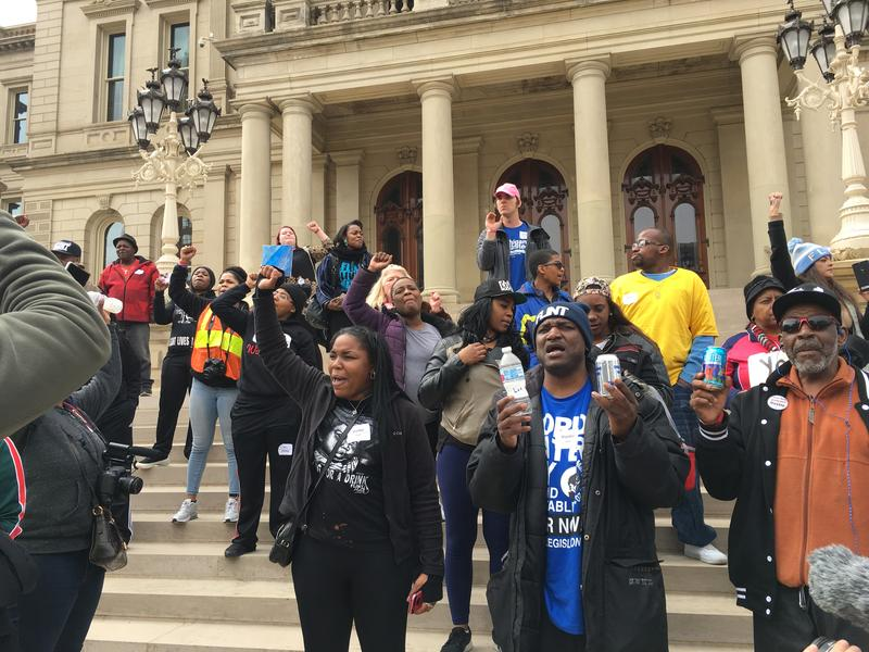 Flint residents stand on the Capitol steps protesting the Snyder administration decision to stop free bottled water delivery to the city.