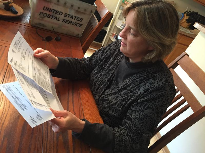 Cathy Cowan Becker looks at electric bill in her Grove City home