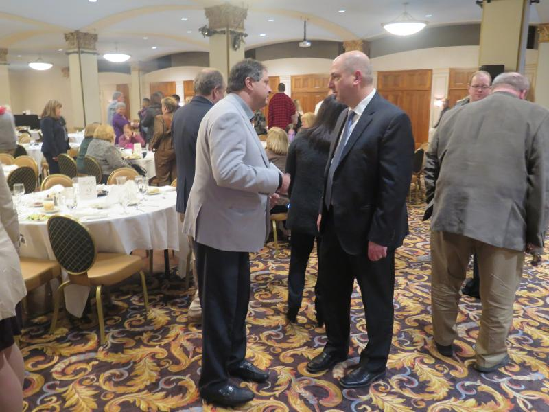 Paul Sracic (right), chair of Youngstown State University's Political Science and International Relations Department, talks with an audience member at the City Club of the Mahoning Valley.