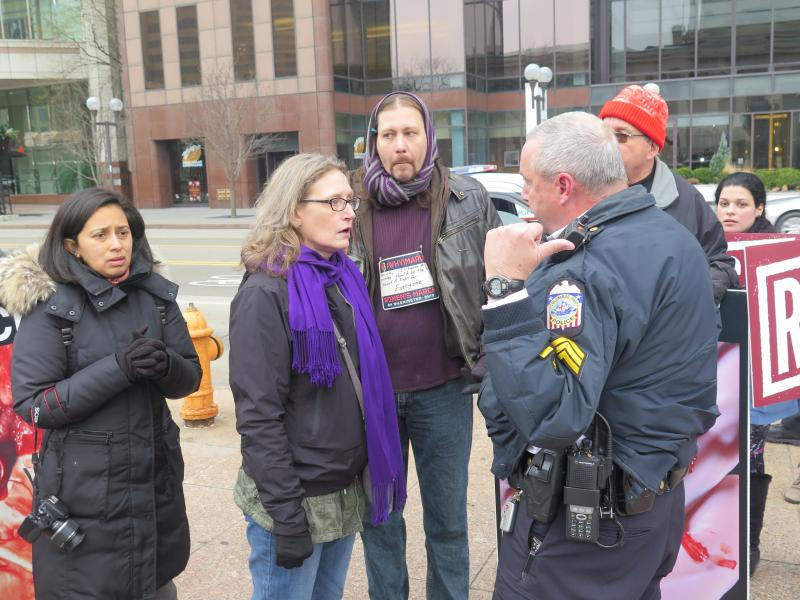 A Columbus police officer talks to two protestors.