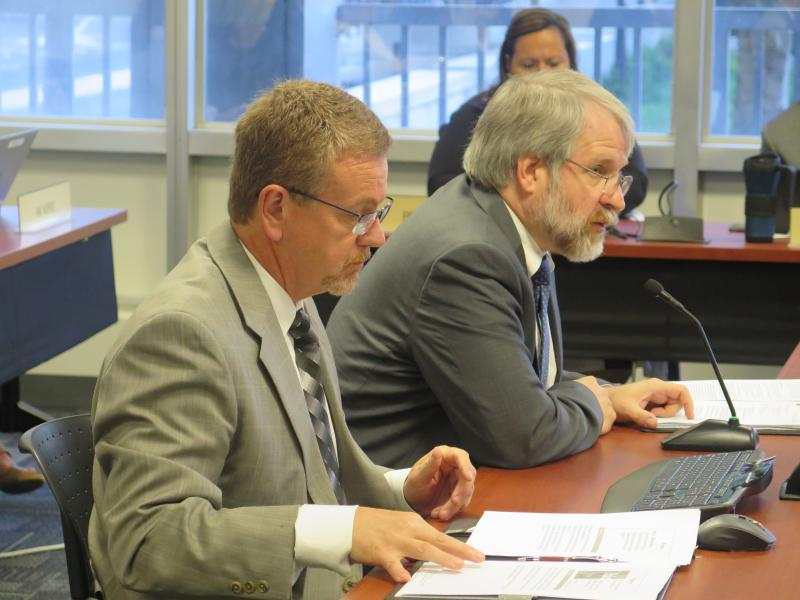 Deputy state school superintendent John Richard and state school superintendent Paolo DeMaria present the testing report to the state Board of Education.