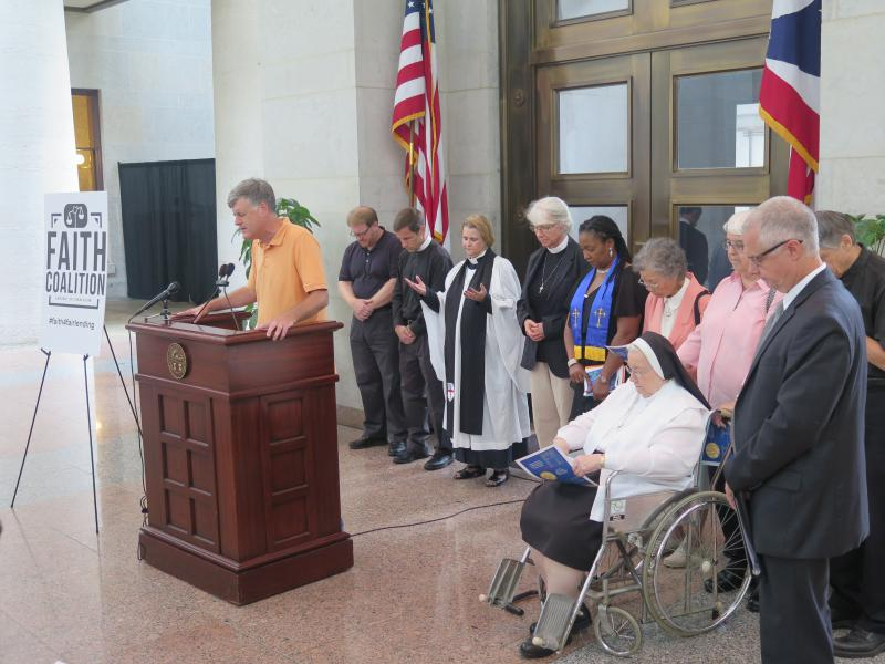 Troy Jackson from the Amos Project leads the group in prayer at the Statehouse.