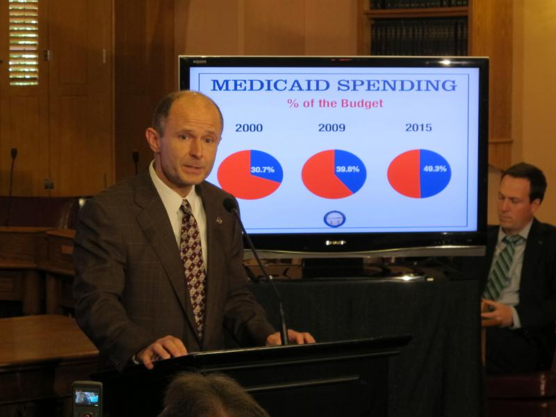 Sen. Dave Burke (R-Marysville) stands before a graph of Medicaid spending in 2013.