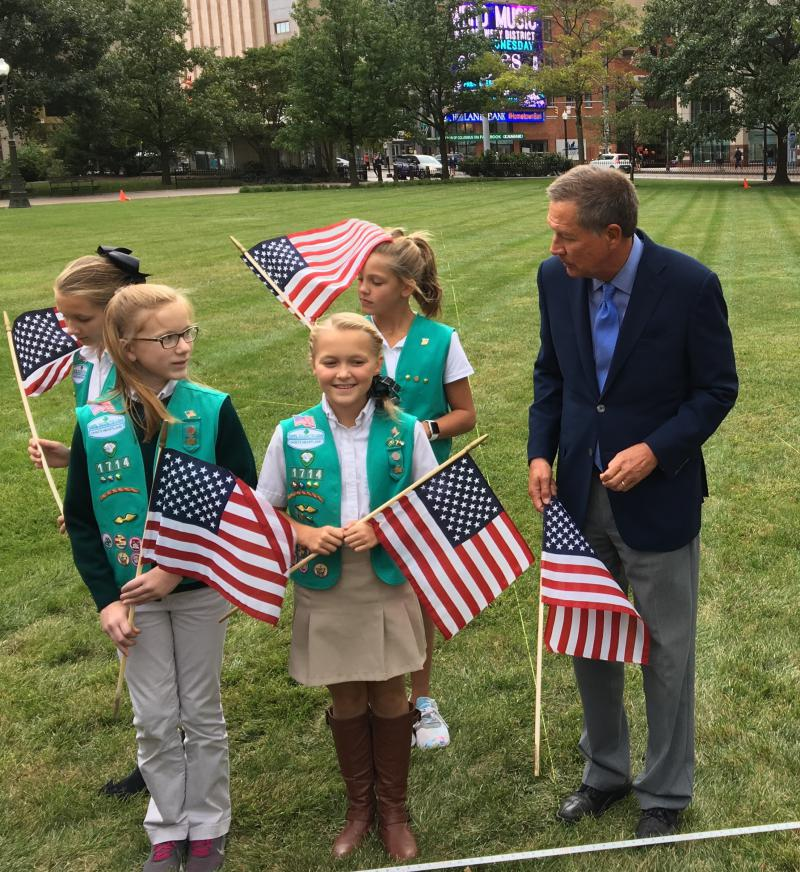 Laine McChesney, Lana Peters, Kayana Skinell and Ava Crane stood alongside Gov. John Kasich as they placed the first flags of the 9/11 memorial at the Statehouse.