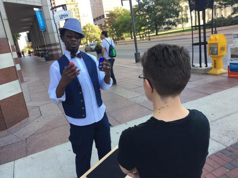 Rory Rennick performs some street magic in Columbus, supporting Issue 2 ahead of an Ohio Elections Commission meeting.