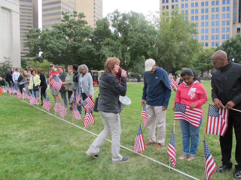 Volunteers place 2,977 flags in a design commemorating the World Trade Towers, the Pentagon and United Airlines Flight 93.
