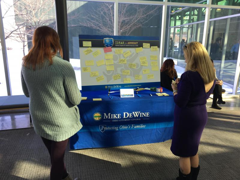 "Conference attendees examine notes on a board labeled ""Ideas for Advocacy""."