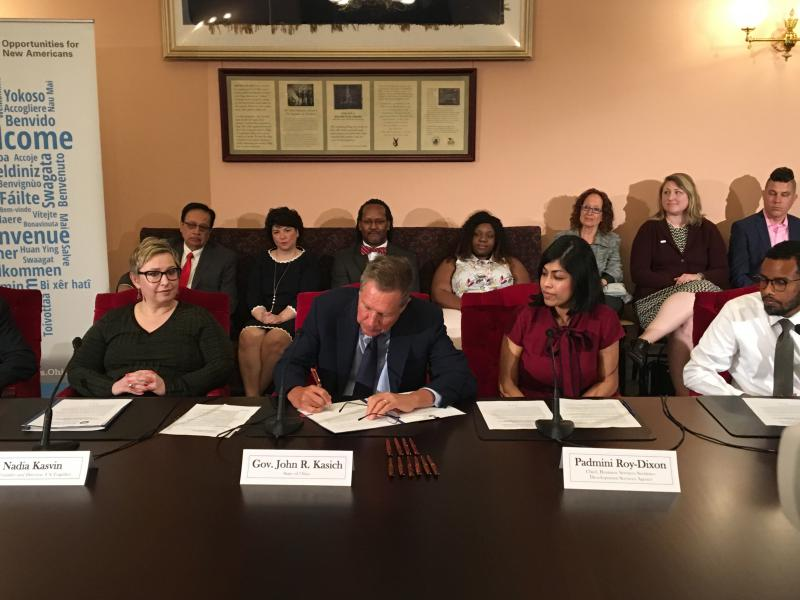 Gov. John Kasich signs an executive order on immigrants in Ohio, flanked by Nadia Kasvin (left), co-founder and director of US Together, Padmini Roy-Dixon (right) with the Ohio Development Services Agency and Nadir Abdi of RESCare Workforce Services.