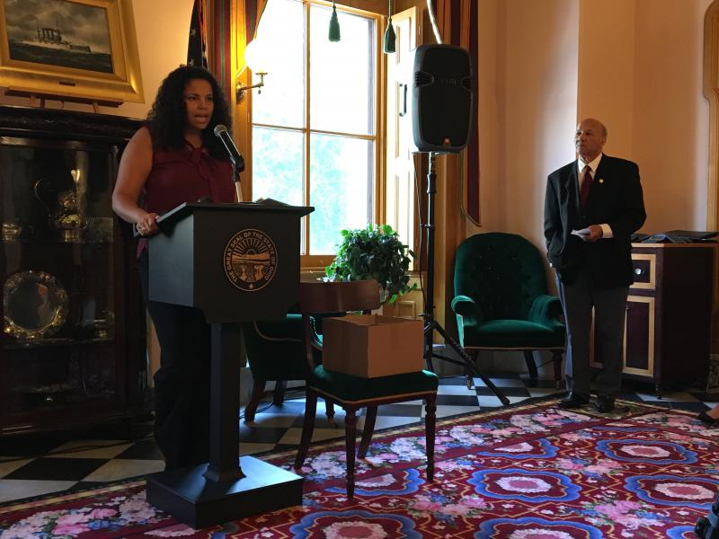 Bianca Edwards speaks at a press conference regarding AT&T's request to drop out of the Lifeline program, as Tom Roberts, the Ohio Conference NAACP president, looks on.
