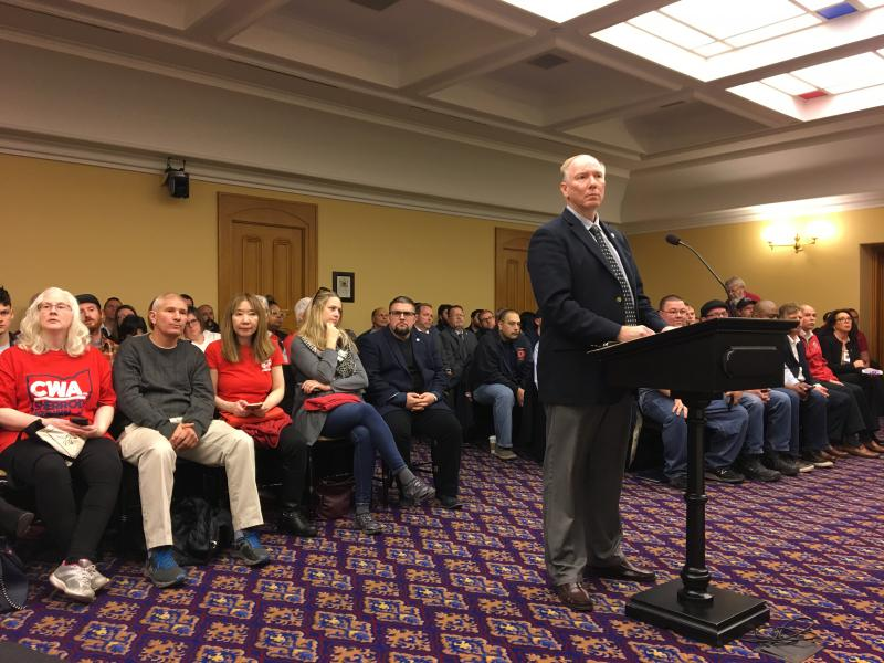 Rep. John Becker (R-Cincinnati) testifies before the House Finance Committee on his bill before a room packed with union members who oppose it.