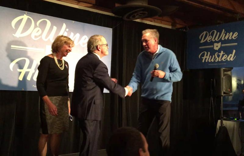Gov. John Kasich (right) shakes hands with Republican candidate for governor Mike DeWine as DeWine's wife Fran looks on.