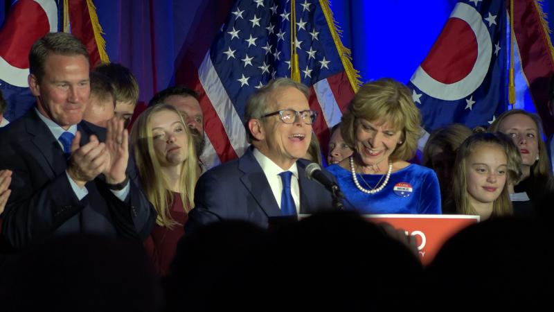 Ohio Attorney General Mike DeWine celebrates winning the race to become Ohio's next governor with running mate Jon Husted (left)