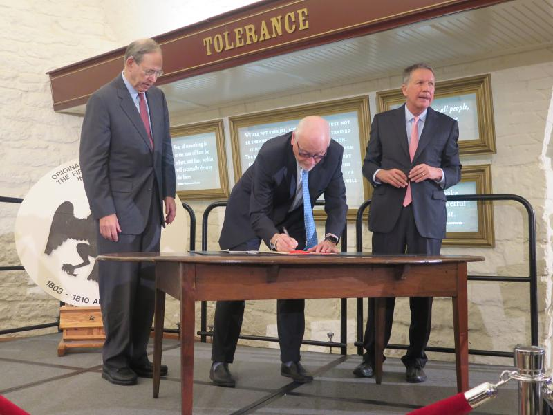 Former Gov. Bob Taft (R), former Gov. Dick Celeste (D) and current Gov. John Kasich (R) sign historic documents on the table the state's first Constitution was signed on Nov. 29, 1802.