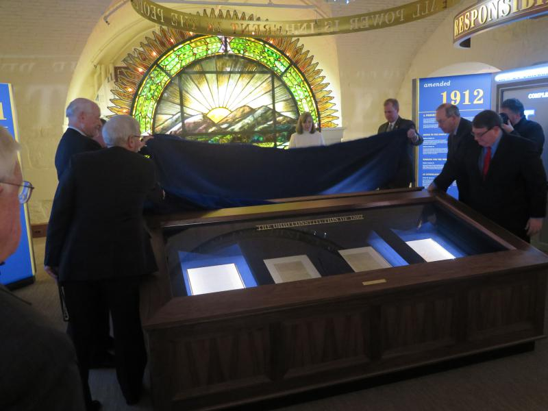 Current and former lawmakers, including former Govs. Dick Celeste and Bob Taft, help unveil the display of Ohio's two constitutions.