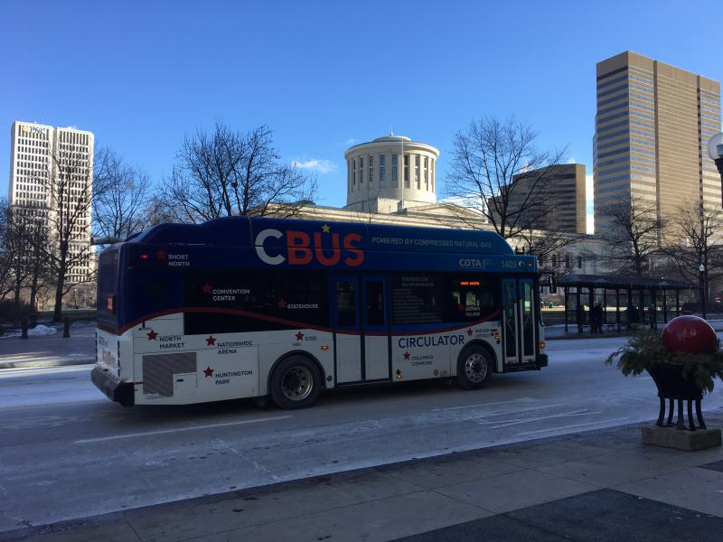 A COTA circulator bus passes in front of the Statehouse.