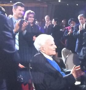 Guests, including Sarah and Todd Palin, applaud Rev. Graham as he enters the room in a wheelchair.