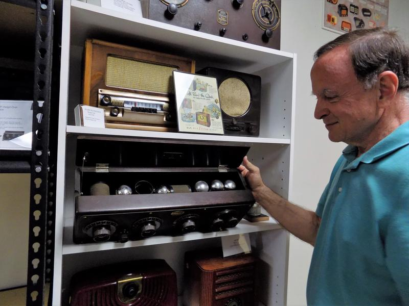 Stuart Smolkin with the Asheville Radio Museum lifts the lid of an Atwater Kent model from the 1920s, showing off the shiny vacuum tubes.