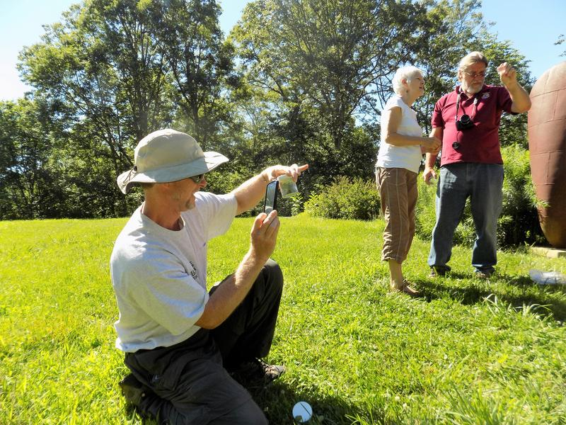 Is it a Rusty Patched?  U.S. Fish and Wildlife biologist  Bryan Tompkins  photogaphs a bee, while USFWS biologist Allen Ratzlaff  and Bee City USA founder Phyliss Stiles look at a bee under a magnifying glass in a garden in Madison County.