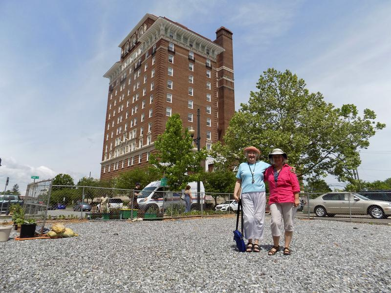 Barbara Gravelle and Clare Hanrahan stand in the empty gravel lot that will soon become a garden thanks to Asheville's community garden program.
