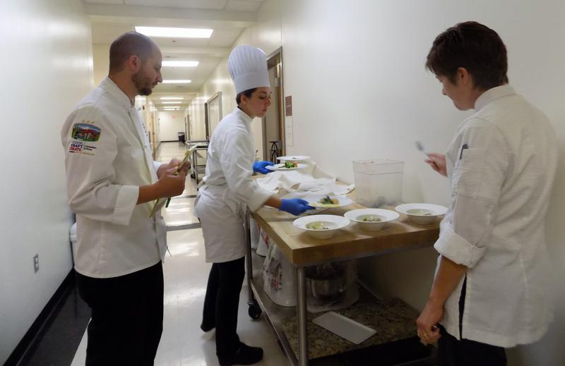 A-B Tech Culinary team captain Jessica Olin brings prepared dishes to chef instructors-coaches Chris Bugher and Bronwyn McCormick for tasting and critique.