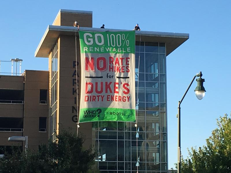 Opponents of the rate hike hung this sign from a parking garage across the street from the Buncombe County courthouse where the hearing took place