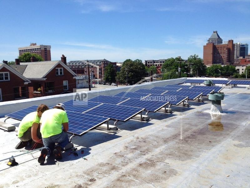 In this June 3, 2015 photo made available by NC WARN, workers install a solar power system on the roof of Faith Community Church in Greensboro, NC.