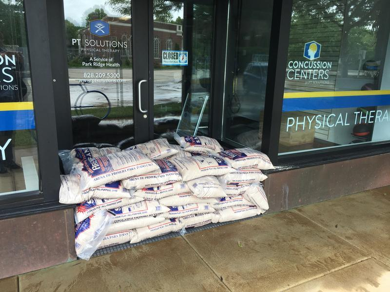 Sandbags outside business at Biltmore Station.  The owners said water came up about 5 inches, leaving the floor and carpets in the business soaked