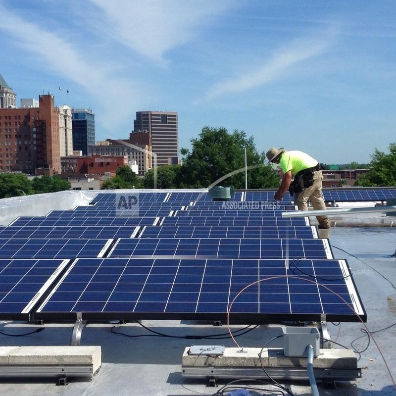 In this June 3, 2015 photo made available by NC WARN, workers install a solar power system on the roof of Faith Community Church in Greensboro, N.C.