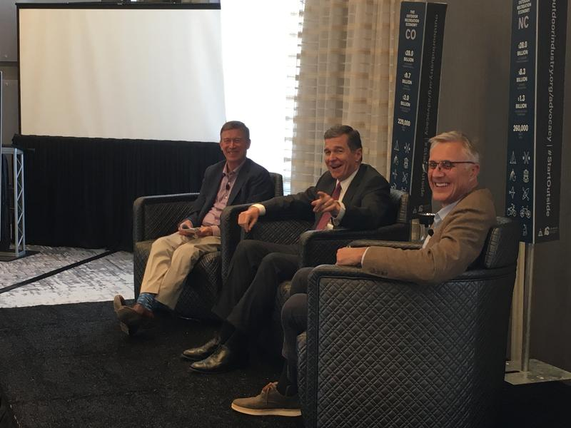 Colorado governor John Hickenlooper, North Carolina governor Roy Cooper, and SylvanSport founder Tom Dempsey during a panel discussion at a conference in Asheville in July