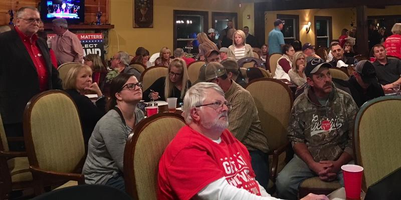 Republicans at the Macon County Republican watch party follow the county results on screen on election night.